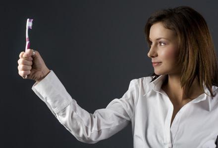 femeie tinand o periuta de dinti