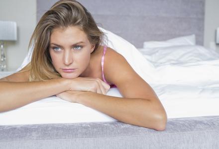 femeie stand trista in pat
