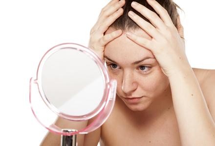 femeie uitandu-se in oglinda