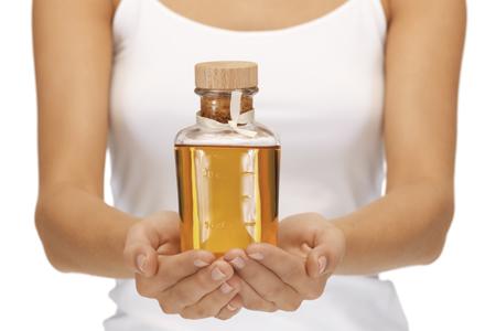 femeie tinand o sticla de ulei in mana