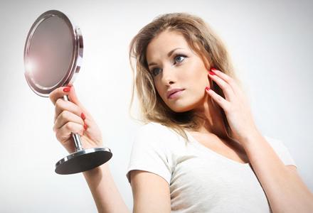 femeie prinvindu-se in oglinda